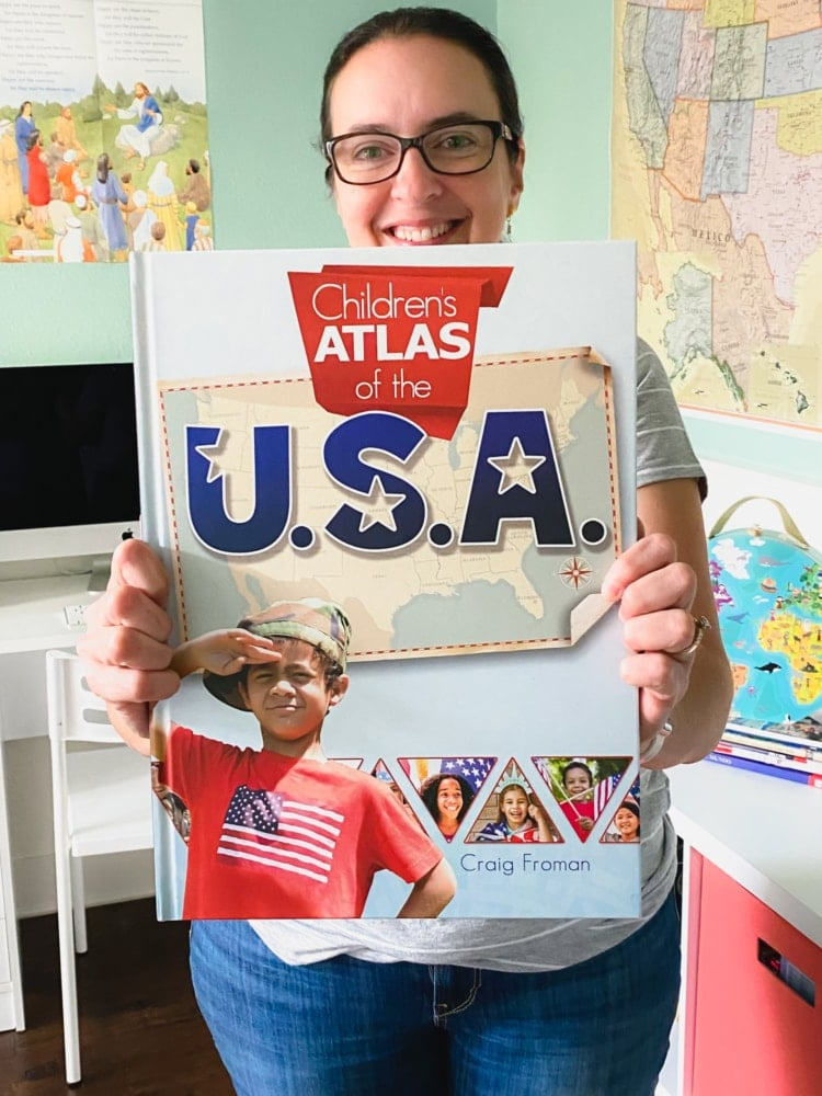a woman holding out in front of her a large children's atlas of the usa book