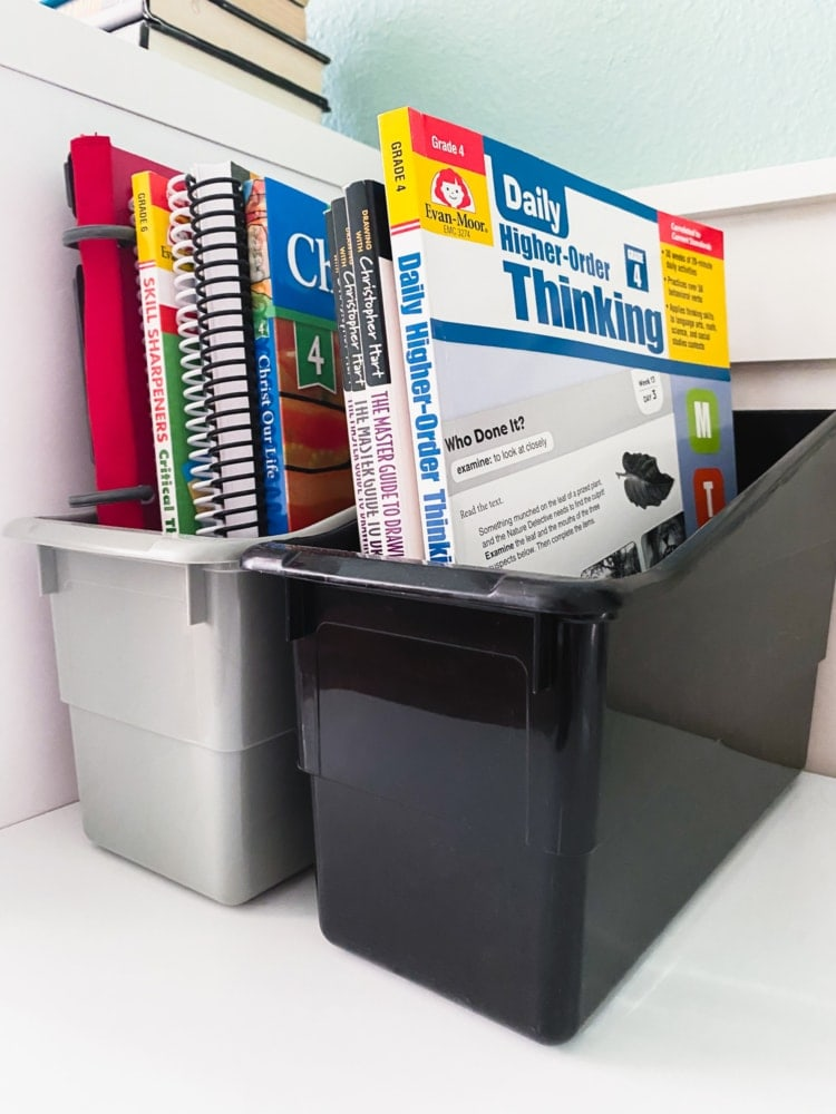 a bin holding several workbooks and notebooks