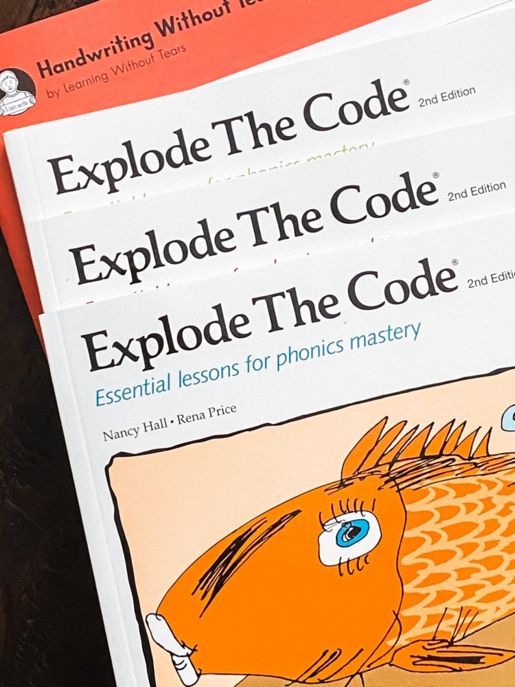 top view of 3 explode the code workbooks and one handwriting without tears workbook