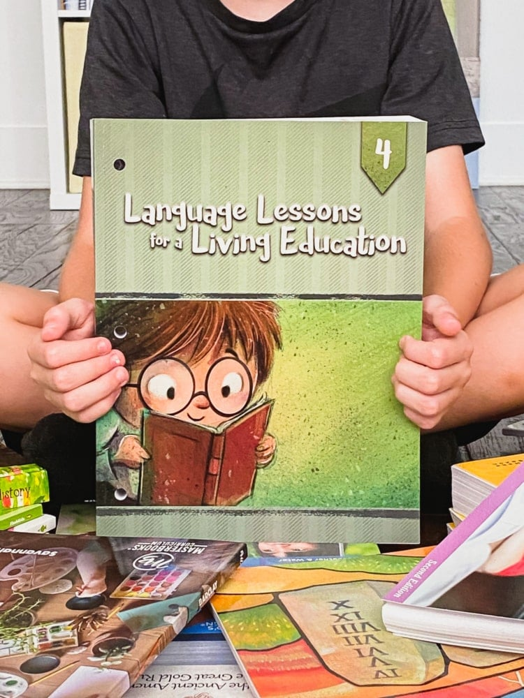 a boy holding a book called language lessons for a living education 4 with more books all around him