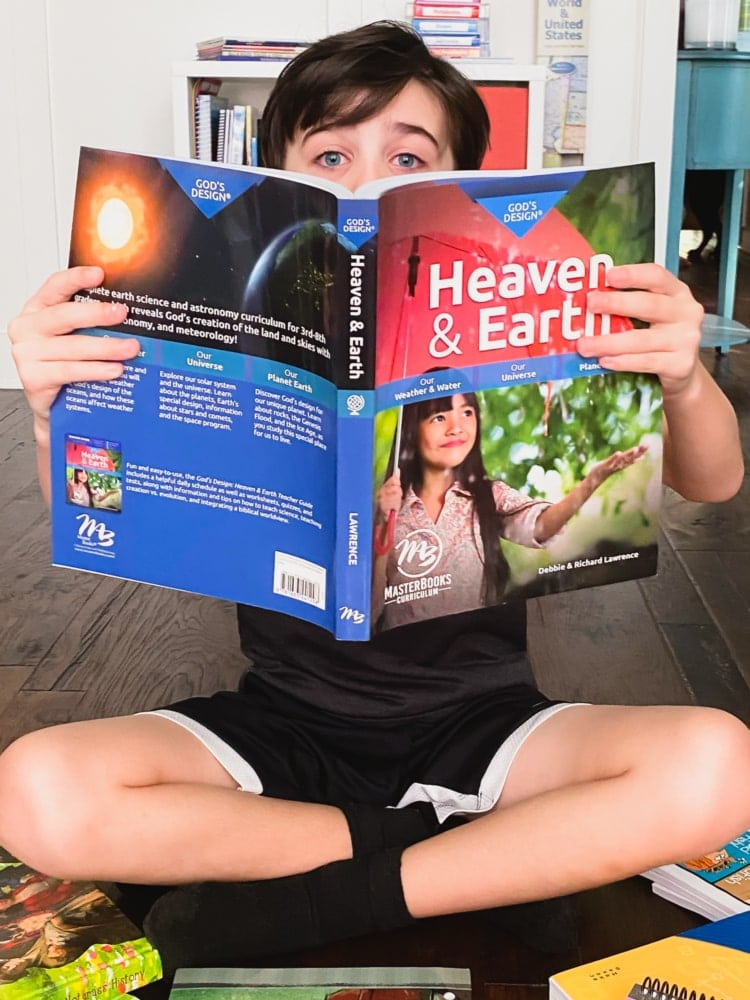 a boy sitting on the floor covering half his face with the book god's design for heaven an earth