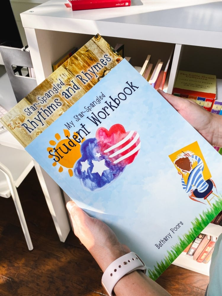 top view of hands holding my star spangled workbook and rhythm and rhymes book from notgrass homeschool history curriculum