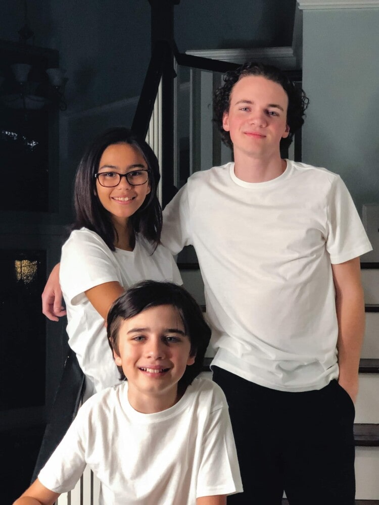 a young boy, teen girl, and teen boy standing on stairs