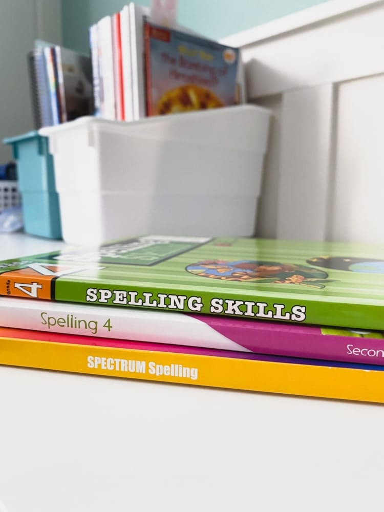 3 stacked spelling workbooks with more books in the background
