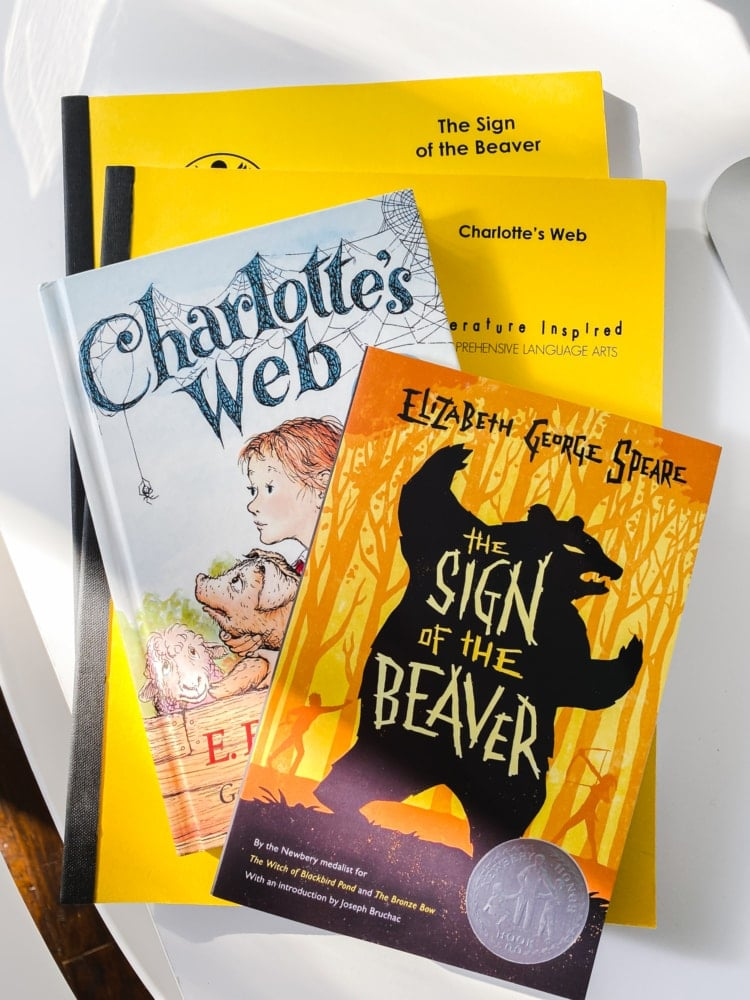top view of charlotte's web book and the sign of the beaver book on top of two total language plus yellow workbooks