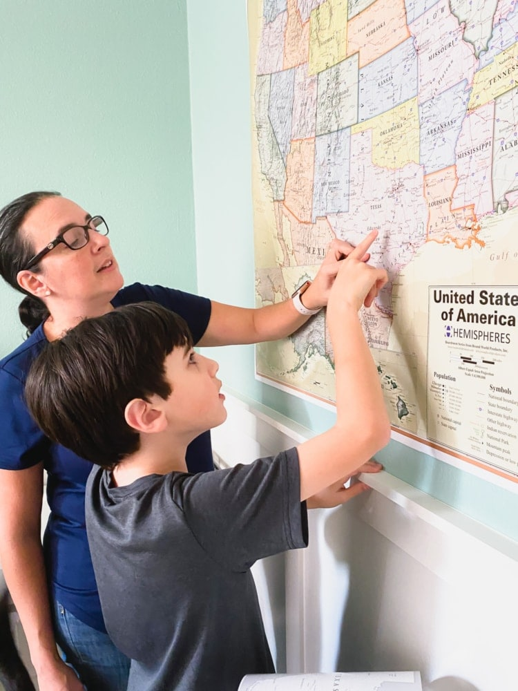 a woman and a boy pointing to Texas on a map on the wall