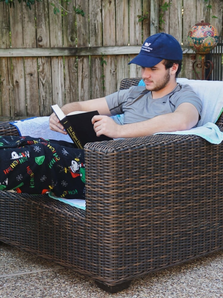highschool boy reading a book for homeschool while sitting in a lounge chair outside on the patio
