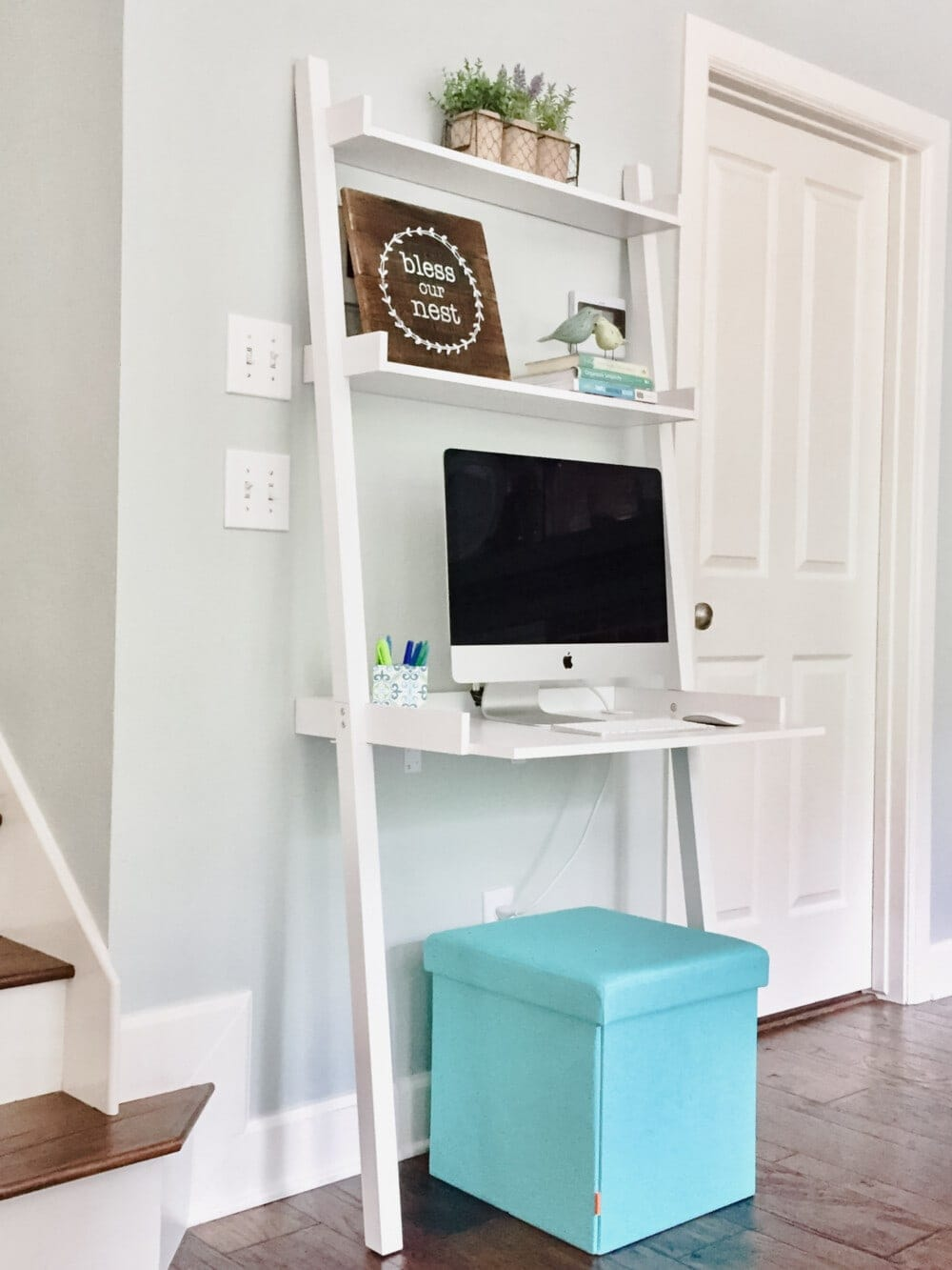 a small ladder desk leaning against the wall with a small popup stool underneath and a desktop computer and decor sitting on the upper shelves