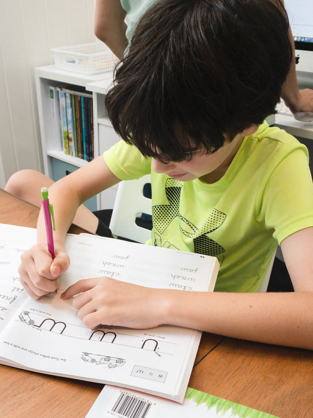 a child practicing handwriting lessons at a table during homeschool