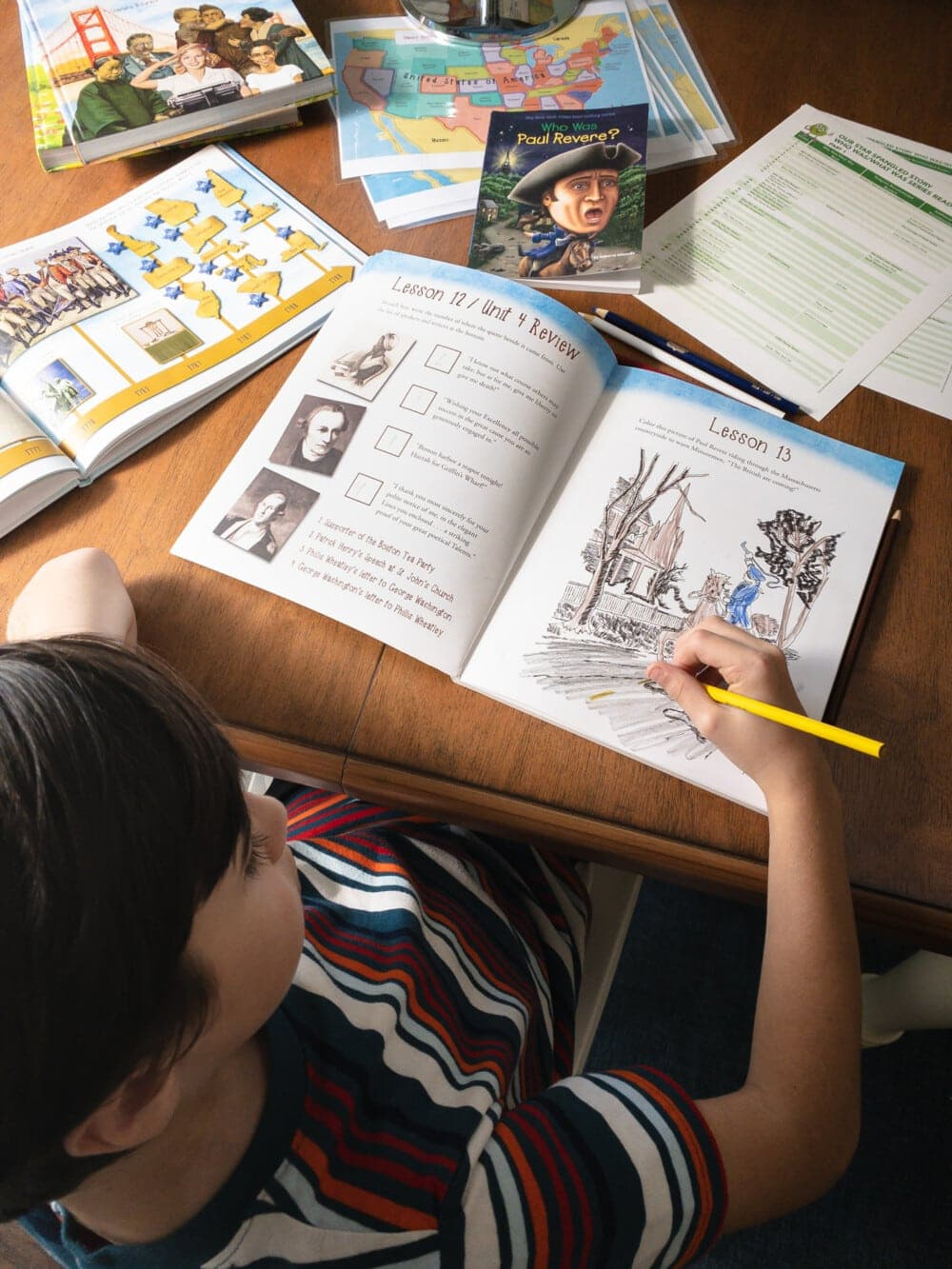 a young boy sitting at a desk with many books, worksheets, and coloring pencils laid out on top of the desk, coloring in a coloring book that is part of the Our Star-Spangled Story curriculum